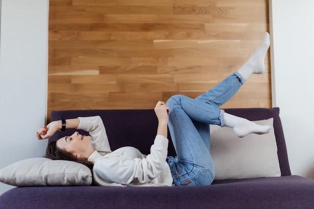 Красивая женщина в белом свитере и синих джинсах развлекается на плохой день