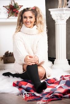 木の床に座っている白いセーターの美しい女性。