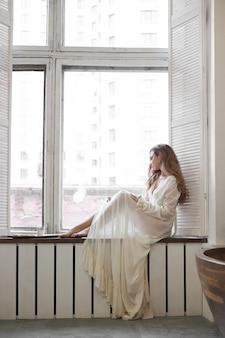 Красивая женщина в белом нижнем белье и неглиже дома в ванной комнате. влюбленная женщина отдыхает