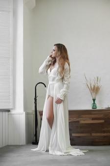 白い下着とネグリジェの美しい女性が自宅のバスルームで