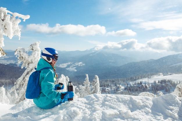 山でお茶を飲む冬服の美しい女性。旅行、レジャー、自由、スポーツの概念。