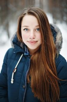 겨울 공원에 서 서, 웃 고, 카메라를 찾고 겨울 옷에서 아름 다운 여자. 배경에 겨울 숲 풍경입니다.