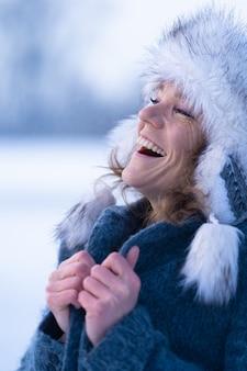 그녀의 얼굴에 미소를 가진 겨울 옷에서 아름 다운 여자
