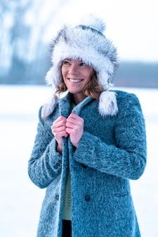 彼女の顔に笑顔で冬の服を着た美しい女性