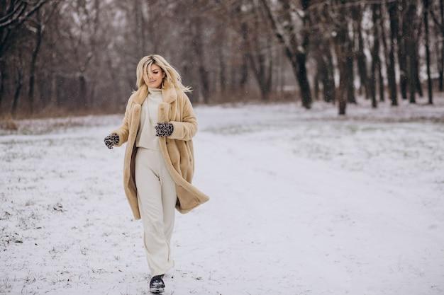 눈이 가득한 공원에서 산책하는 겨울 코트에서 아름 다운 여자