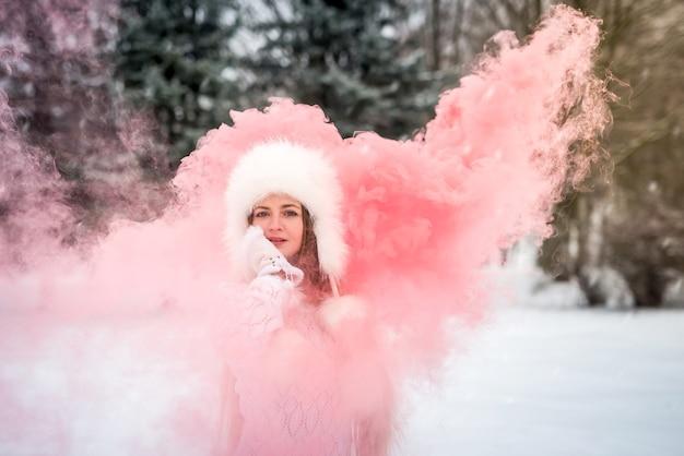 붉은 연기 폭탄을 들고 겨울 공원에서 아름 다운 여자