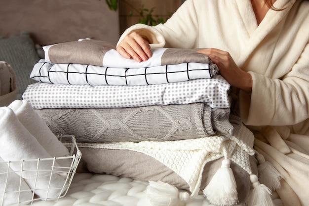 冬の厚い暖かいローブの美しい女性が座って、ベッドリネンと白いバスタオルをきれいに折りたたんでいます。きれいな洗濯物の整理と仕分け。有機および天然の綿織物。製造。