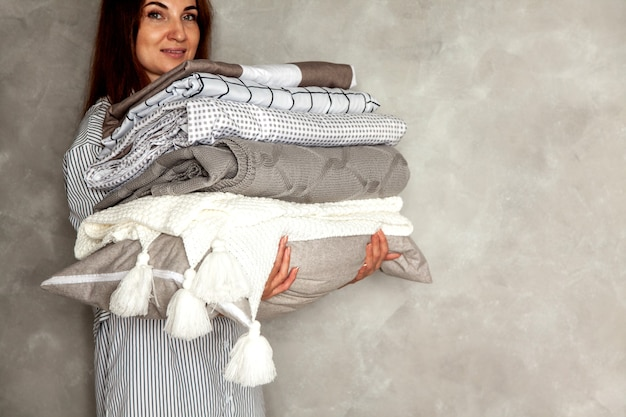 Сидит красивая женщина в толстом теплом зимнем халате и аккуратно складывает постельное белье и белые банные полотенца. организация и сортировка чистого белья. текстиль из органического и натурального хлопка. производство.