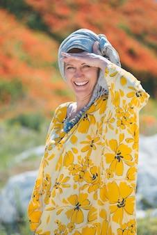 非常に暑い天気の草原フィールドで黄色のドレスを着た美しい女性。