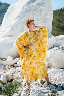 非常に暑い砂浜で黄色のドレスを着た美しい女性。遠くを見る