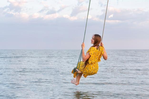 Красивая женщина в желтом платье сидит на качелях веревки над морем. успокойте расслабьтесь одиночество.