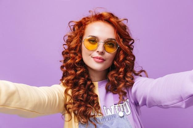 노란색 선글라스에 아름다운 여자가 셀카를 찍고 라일락 벽에 정면을 본다.
