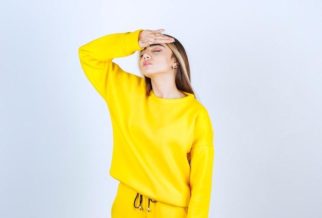 白い壁に頭痛を持っている黄色のスウェットスーツの美しい女性