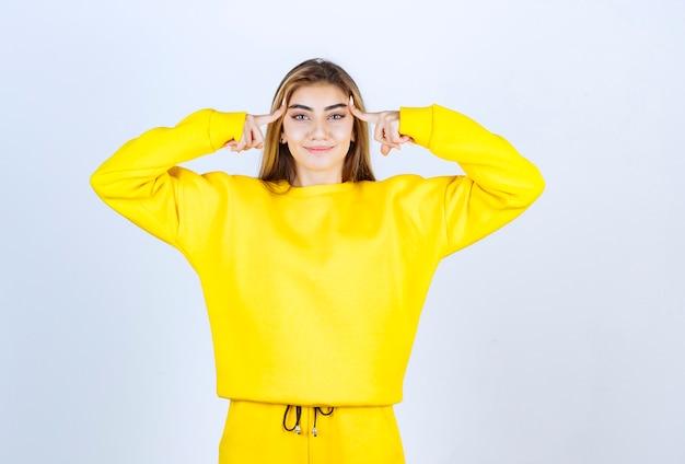 노란 운동복을 입은 아름다운 여성이 흰 벽 위에 서서 포즈를 취하고 있다