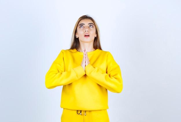 노란 운동복을 입은 아름다운 여성이 흰 벽 위에 서서 기도하고 있다