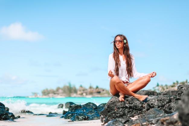 Красивая женщина в положении йоги во время тропического отпуска