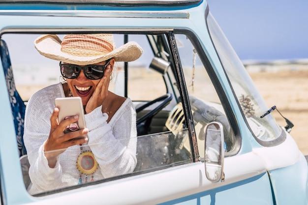古いビンテージのトレンディなバンの中にいる美しい女性が、喜びと驚きで電話を見る