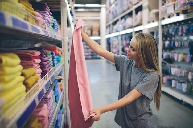 Красивая женщина осматривает и покупает полотенца в супермаркете.