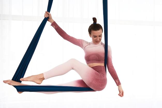 아름다운 여성 강사는 반중력 요가의 포즈인 푸른 공기 해먹에 앉아 있고, 밝은 창 앞의 해먹에서 공중에 떠 있는 소녀입니다.