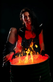 Beautiful woman and iron barrel with fire inside