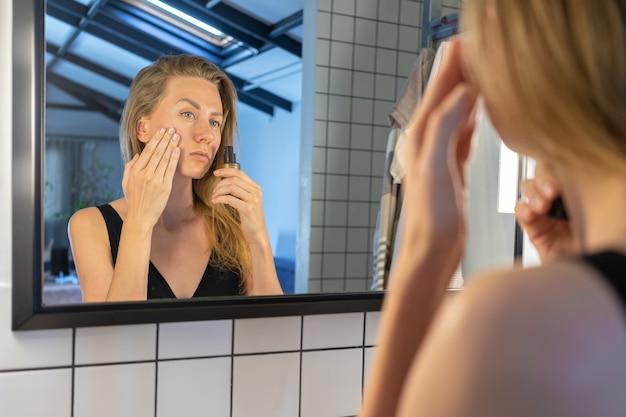 美しい女性は、バスルームの鏡の前に立って、顔の皮膚保湿剤、クリームを適用しています。顔の美容トリートメント。