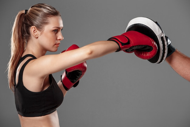 Beautiful woman is boxing on gray background