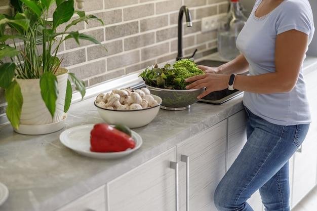 아름 다운 여자는 그녀의 집 부엌에서 맛있는 요리를 요리