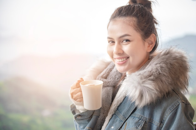 Beautiful woman is drinking coffee in the morning with nature background