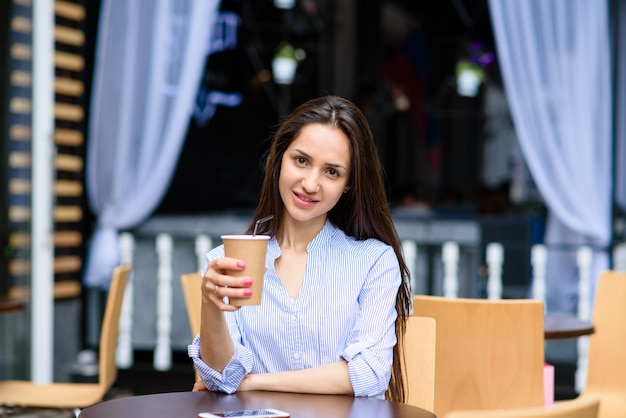 Beautiful woman is drinking coffee in a street cafe.