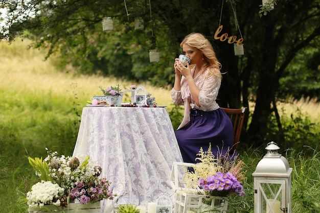 Beautiful woman is drinking tea from vintage teacup in nature.