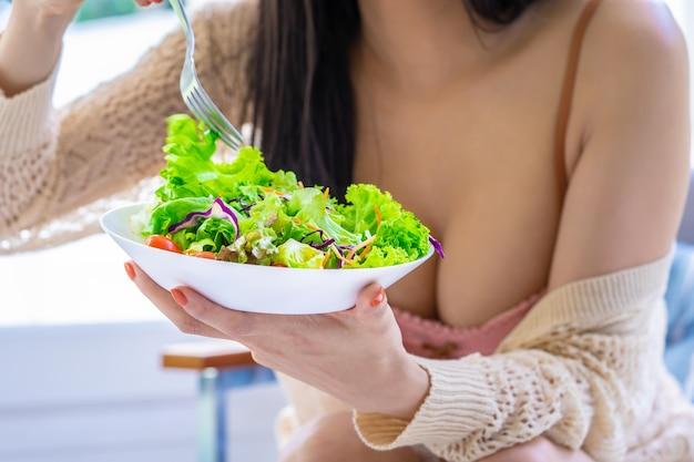 美しい女性は健康的で形のライフスタイルの概念のためにグリーンサラダを食べています。
