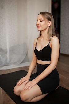 아름 다운 여자는 검은 옷에 검은 양탄자에 앉아 집에서 명상에 종사하고있다
