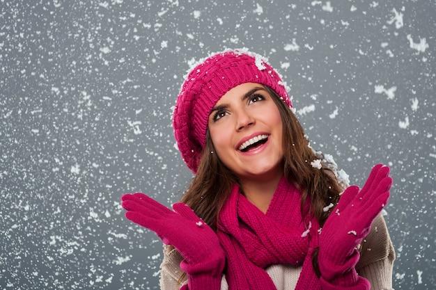 Красивая женщина счастлива от снега в зимнее время