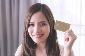 Beautiful woman is holding a golden credit card for financial concept