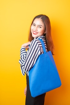 Beautiful woman is holding blue cloth bag
