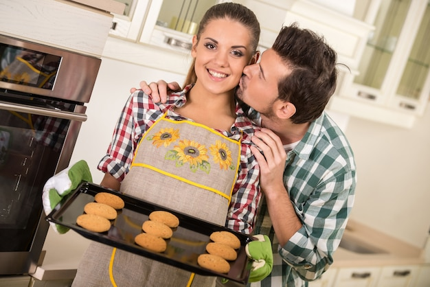 Beautiful woman is holding hot roasting pan with cookies.