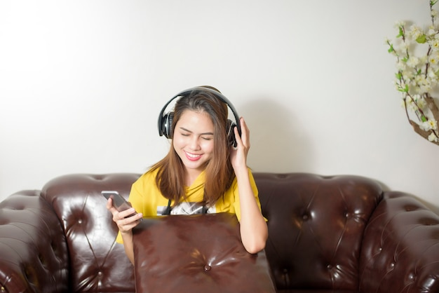 Beautiful woman is listening music in home