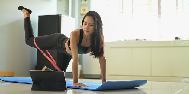 A beautiful woman is looking into a computer tablet while doing an exercise in a comfortable living room.