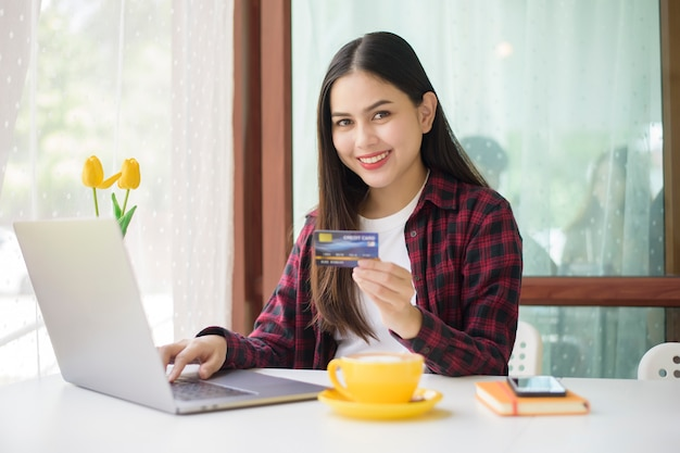 Beautiful woman is online shopping with credit card in coffee shop
