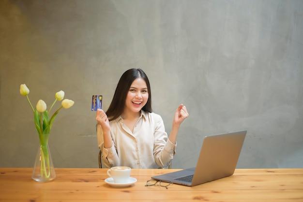 美しい女性はコーヒーショップでクレジットカードでオンラインショッピングをしています