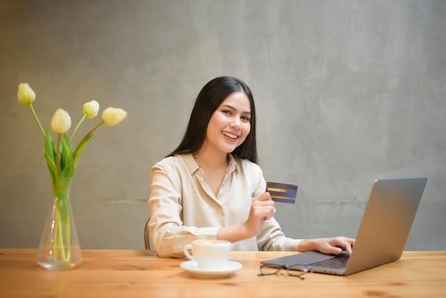 아름 다운 여자는 커피 숍에서 신용 카드로 온라인 쇼핑