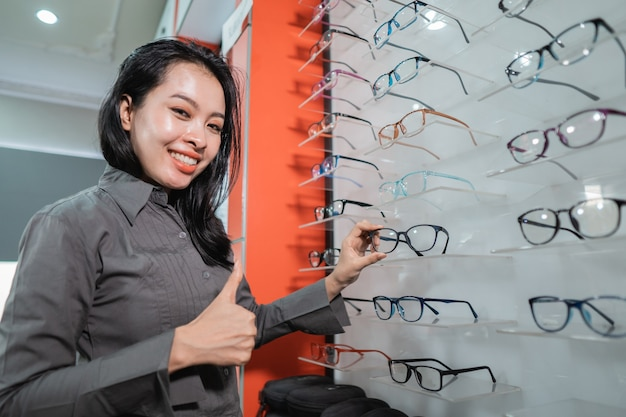 A beautiful woman is posing holding glasses in a window in an eye clinic