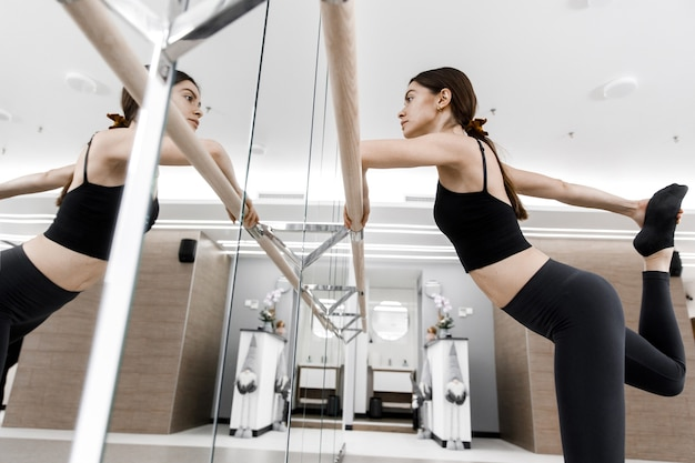 Beautiful woman is practicing ballet moves standing by bar against mirror in dance studio.