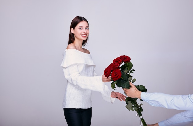 A beautiful woman is presented with a large bouquet of red roses.