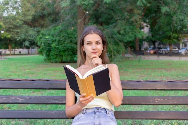 Красивая женщина читает книгу и думает о чем-то на скамейке в парке. у девушки есть мысли и идеи