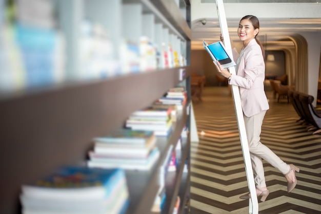 Beautiful woman is reading books in library