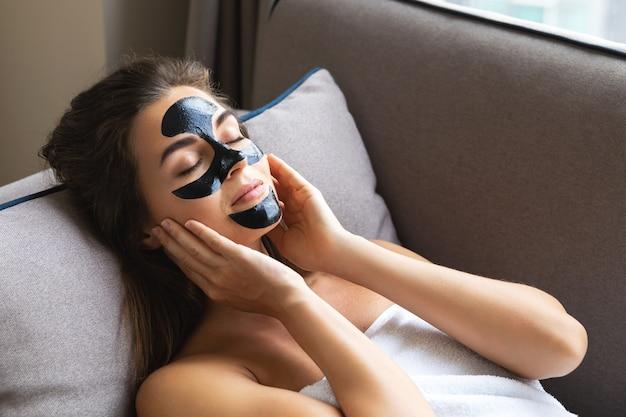 Красивая женщина отдыхает дома с черной отшелушивающей маской на лице
