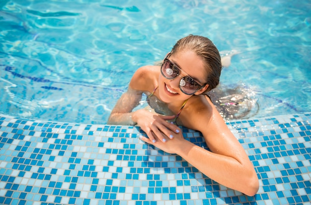 Beautiful woman is relaxing in swimming pool.