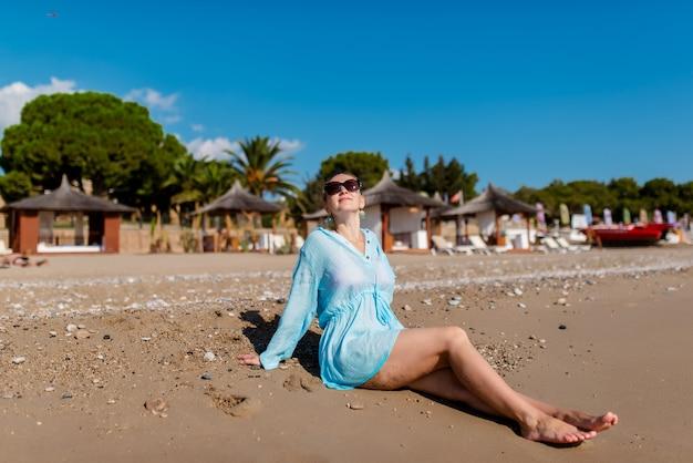 美しい女性はビーチで休んでいます。