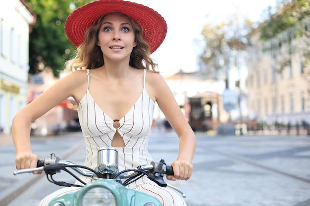 Beautiful woman is riding on motorbike city street, traveling.